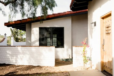 a Spanish-style home with a white brick wall at the entrance