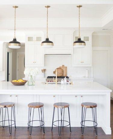 Modern coastal kitchen ideas in white kitchen three brass and black pendant lights