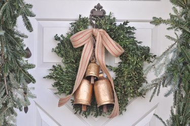 Christmas Door Decorations with Evergreen wreath with gold bells and ribbon on white door.