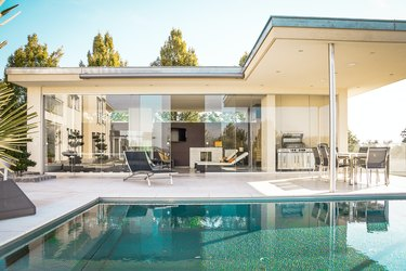house with glass walls and pool nearby