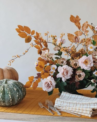 fall kitchen decor with yellow table runner with yellow and pink flower arrangement on top