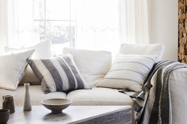 white living room with striped accent pillows and throw blanket