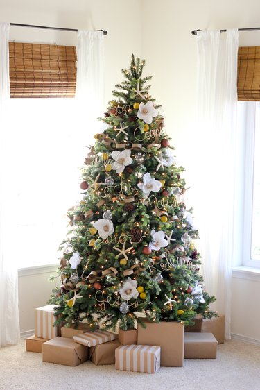 coastal Christmas tree with giant faux magnolia, glass bulbs, and gold wire