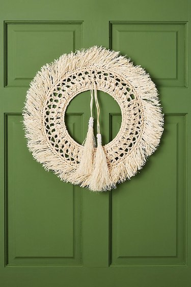 Christmas Door Decorations with Straw wreath on green door.