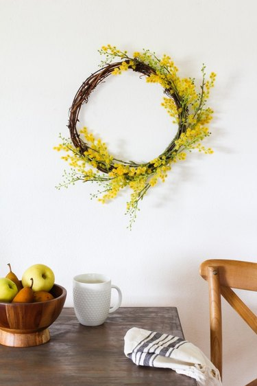 fall kitchen decor with grapevine and yellow wreath hanging above a kitchen table