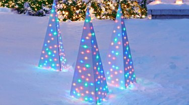 exterior Christmas decorations with Multi colored lights inside modern Christmas trees outside on patch of snow.