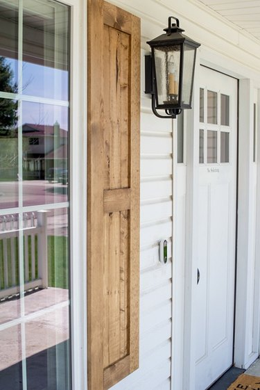 Flat panel exterior shutter style in natural wood finish on white exterior next to lantern sconce