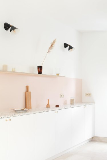 Contemporary kitchen style with pink backsplash and geometric lights