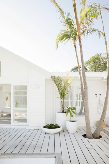 White exterior beach house colors with deck and palm trees