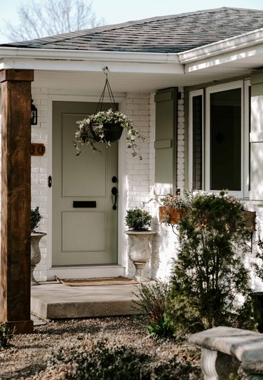 Soft green exterior house paint on front door and shutters with painted white brick exterior