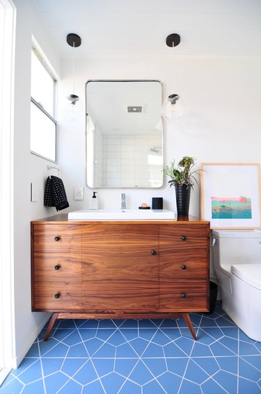 midcentury bathroom lighting idea with geometric glass pendants and blue patterned tile flooring