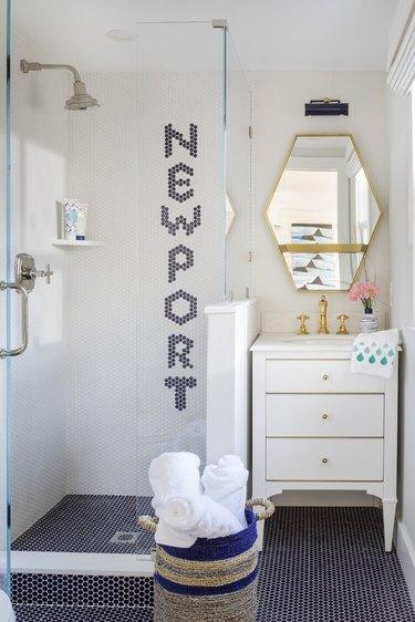 Navy blue penny tile coastal flooring idea in bathroom with white vanity