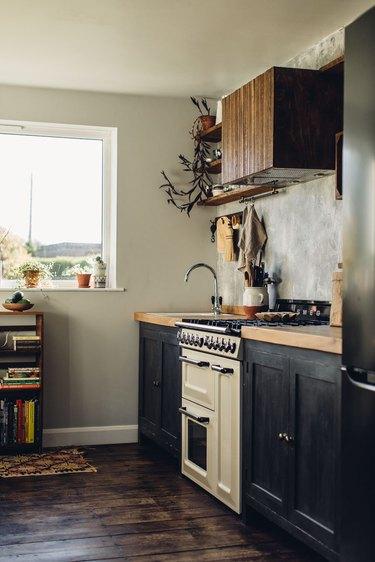 rustic kitchen with white retro stove and dark cabinets