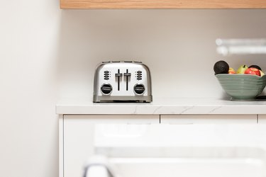 Toaster on counter near fruit bowl