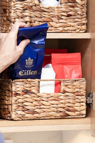 Natural woven baskets holding coffee beans in cabinet