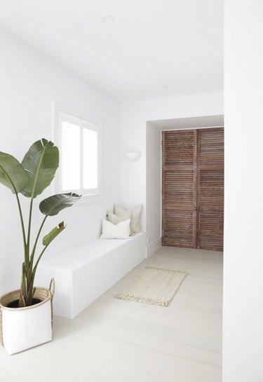 Bleached hardwood coastal flooring idea in corner of home with window seat