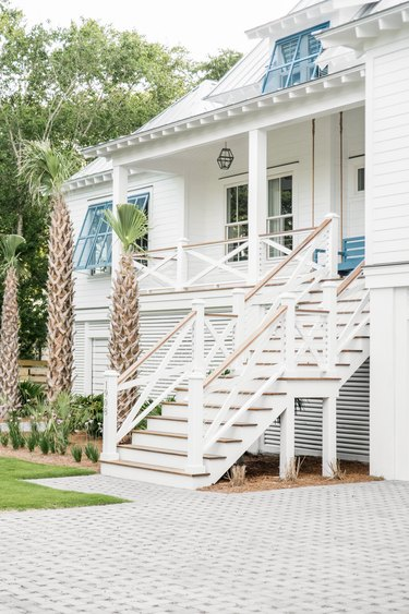 Blue and white exterior beach house colors with driveway and palm trees