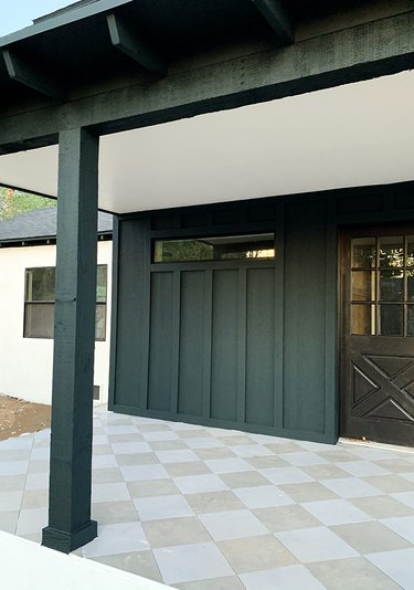 Dark forest green exterior house paint with checkered floor and black front door