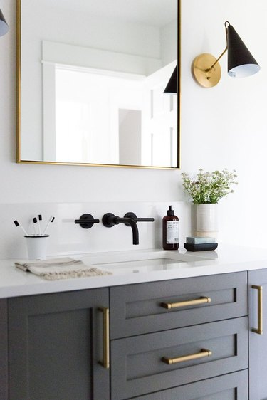 white and black midcentury bathroom lighting idea with wall sconces on either side of vanity mirror