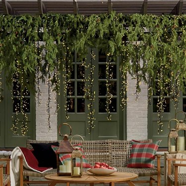 exterior Christmas decorations with Draped evergreen garland with meteor lights, wicker couch, pillows and wood outdoor coffee table, french doors.