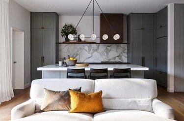 kitchen island lighting idea with ten light chandelier and marble backsplash