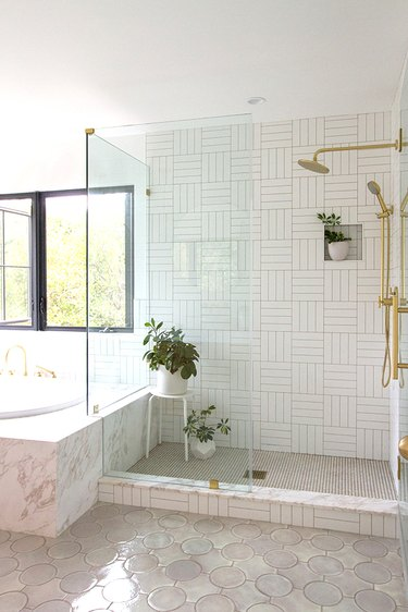 walk-in shower with potted plants and white patterned tile