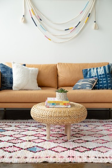 IKEA floor pad as a coffee table, tan leather couch, bohemian pillows and wall tassel hanging.