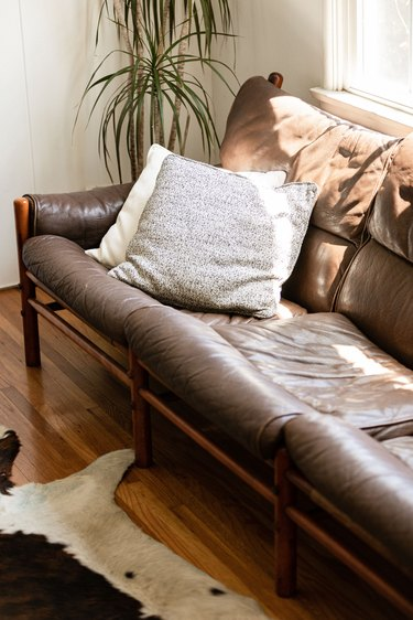 Brown leather couch with wood legs