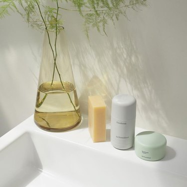 By Humankind beauty products on a sink with plant nearby