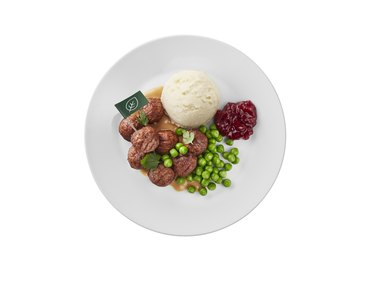 plate with plant balls, potatoes, peas, and lingonberry jam