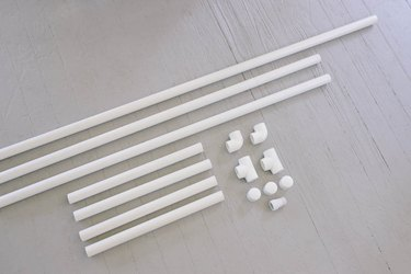 PVC pipe cut to various sizes laid next to elbow and tee connectors and caps