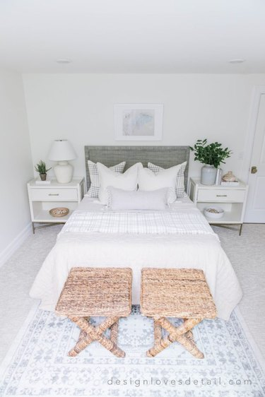 Modern coastal bedding idea with linen bedding and seagrass stools