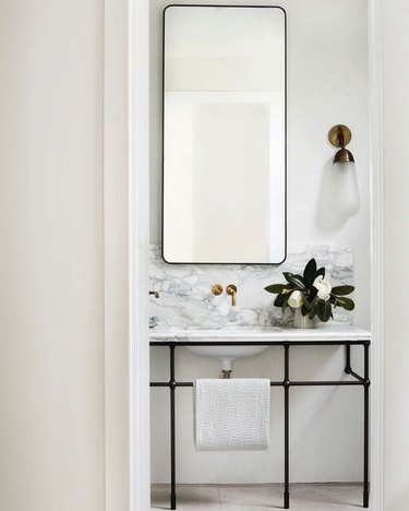 console bathroom sink with marble countertop and backsplash and black metal legs