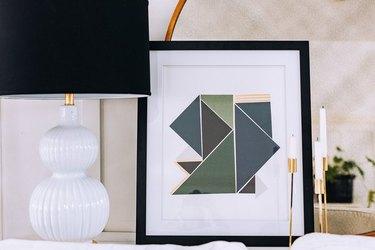 Scrapbook paper artwork next to white and black lamp.