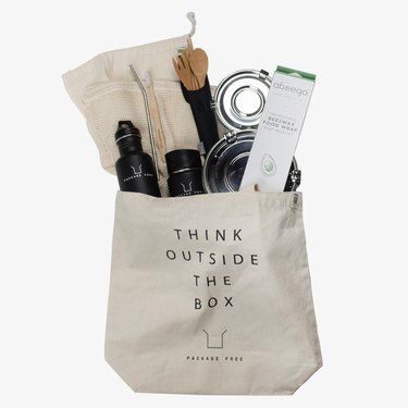 """Tote bag with """"think outside the box"""" in text and a variety of eco-friendly items inside"""