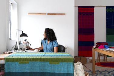 Hana Getachew Bolé Road Textiles sitting at desk surrounded by colorful patterned textiles