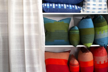 built-in bookcase filled with colorful patterned accent pillows