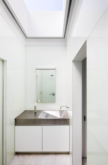 stainless steel bathroom sink in white space with white vanity cabinet and skylight