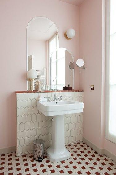 pedestal bathroom sink with pink walls and patterned floor tile