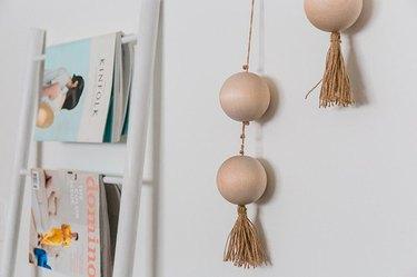 Bead boho wall hanging on wall next to magazines.