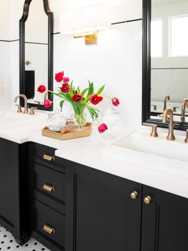 black vanity cabinet with brass hardware and his and hers sinks