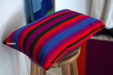 colorful striped pillow on wood stool
