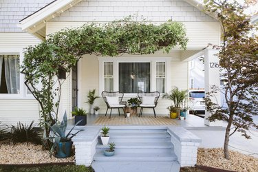 white home exterior with light blue porch steps and greenery