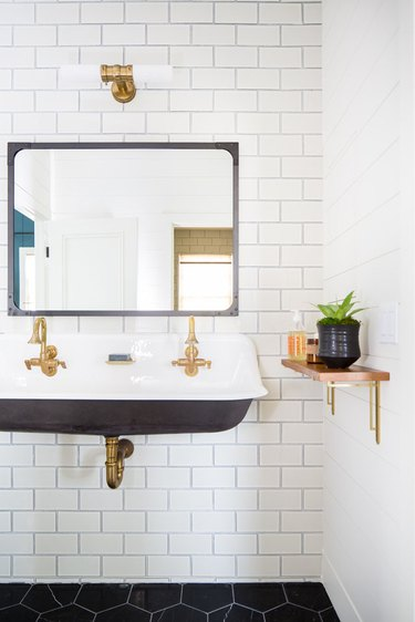 wall-mounted trough bathroom sink on white subway tile with brass fixtures