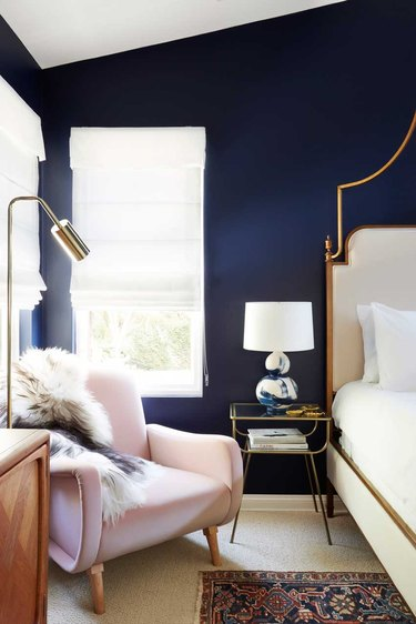 navy blue bedroom with pink velvet lounge chair