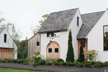 white home exterior with wooden doors and gray roof