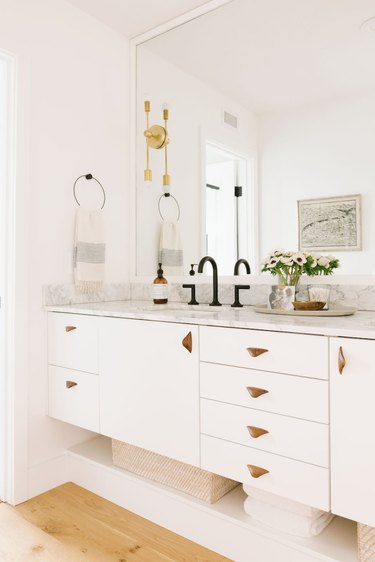 undermount bathroom sink with white cabinets and marble countertop