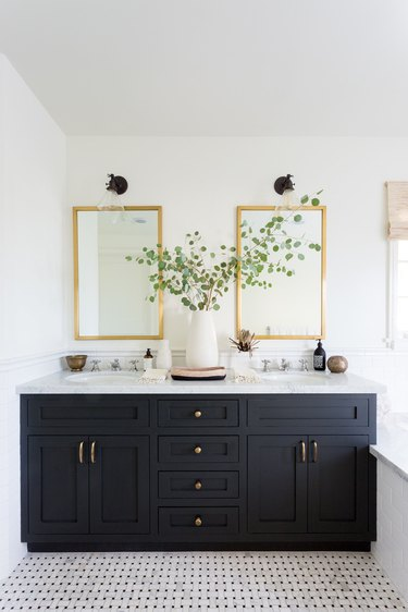 black vanity cabinet with black and white mosaic flooring