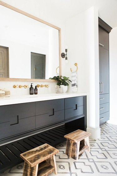 black vanity cabinet with black and white tile flooring