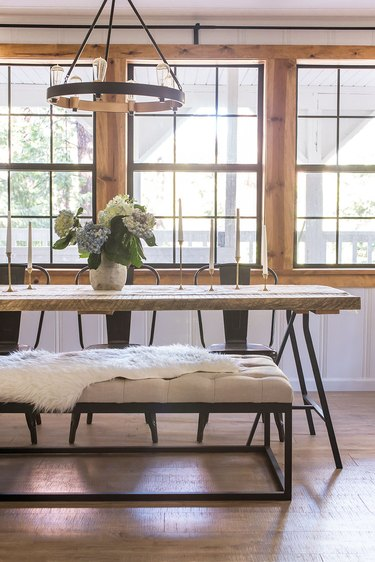 Large windows behind a wood and metal dining table